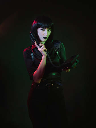 Woman in black clothes on a black background with green light. She holds a phone in one hand and a telephone receiver in the other hand, which is brought to her ear.