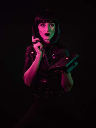 A girl on a black background, in a green-pink light, holds a telephone set in one hand and a telephone receiver in the other. Her gaze is directed up and to the side. Stok Fotoğraf