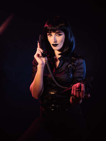 A girl on a black background holds a telephone in her hands, the receiver of which is close to her ear. She looks into the frame with a grin