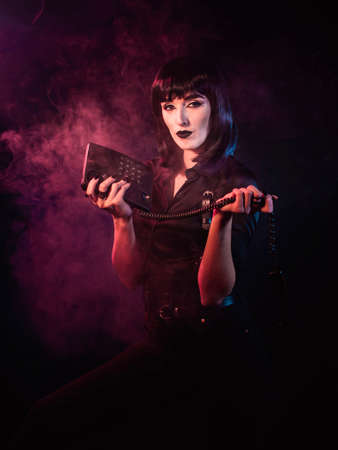 Girl on a black background with red light and smoke. She is holding a telephone, the handset of which is hanging from a cord. The girl looks carefully into the frame.