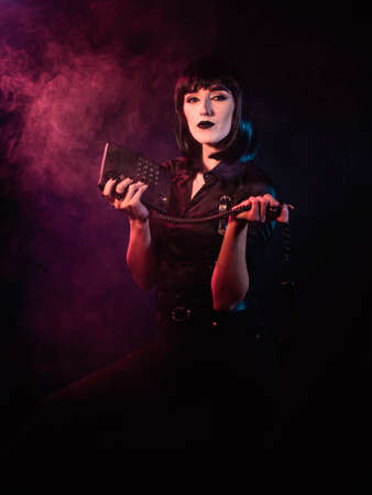 A girl on a black background with red and blue light holds a telephone set in her divorced hands, her gaze directed towards the camera. Archivio Fotografico