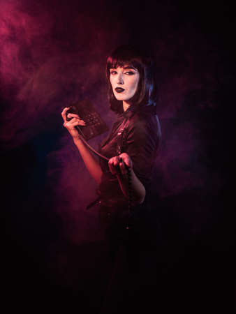 Girl on a black background with red and blue light and smoke. She is turned sideways and holds a telephone set in her divorced hands.