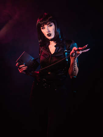 Girl on a black background with red and blue light. She holds in one hand a telephone set, and in the other hand a telephone receiver hanging on a cord.