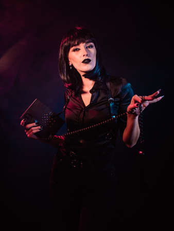 A girl on a black background, in black clothes and a black wig, holds a telephone set in her divorced hands and looks haughtily into the frame.