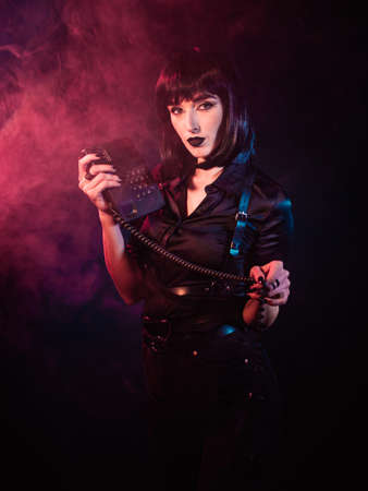 woman on a black background with red and blue light and artificial smoke. She holds in her divorced hands a telephone, the receiver of which hangs on a cord.