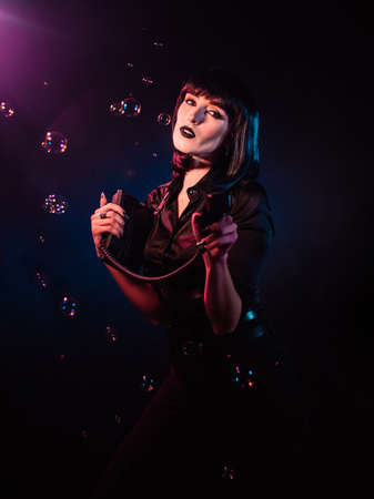 woman on a black background with pink and blue light and soap bubbles. She holds a phone in her hands, which she points to the frame.