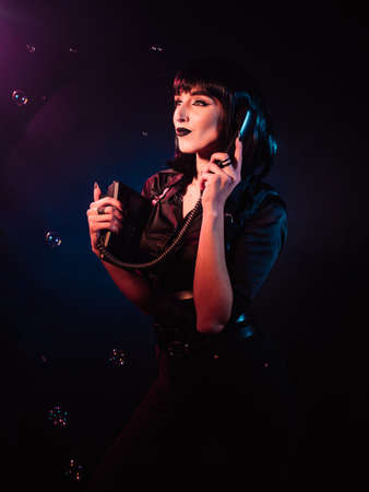 woman on a black background with pink and blue light and soap bubbles. She has a telephone in her hands. She looks away and smiles.