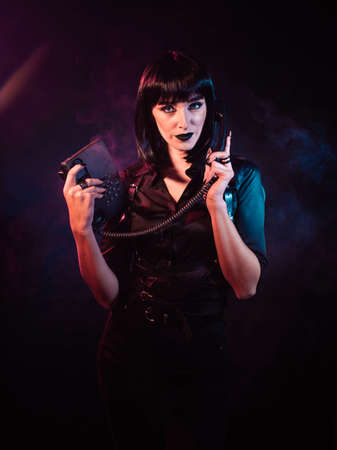 woman on a black background with pink-blue light and a slight haze. She is holding a telephone set, the receiver of which is pressed to her ear.