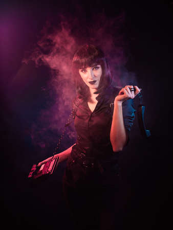 girl on a black background with pink-blue light and a slight haze. She is holding a telephone in her hands.