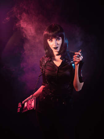 a girl with black hair in a black shirt dressed in a harness holds a telephone device in her hands, illuminated in pink Archivio Fotografico