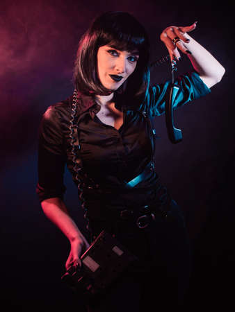 a girl in color light with black hair on a dark background, holds a receiver on a cord from a landline telephone with her fingers
