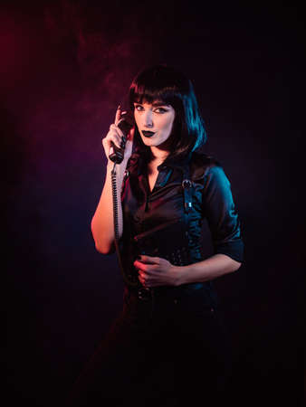 a girl in colored light, with black hair in a harness, holds a landline phone to her ear