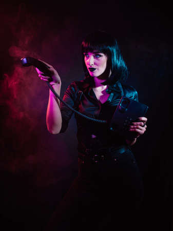 a girl in colored light, with black hair in a harness, points to the side with a receiver from a landline phone Archivio Fotografico