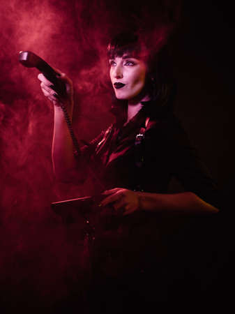 girl in a harness with black hair and a shirt in red light and smoke, points and looks to the side