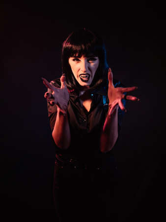 Girl on a black background in the image of a vampire with fangs. She hisses and grimaces, opens her arms to the camera.