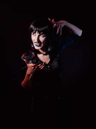 A woman on a black background, wearing a black wig and black clothes, she looks at the light and smiles viciously, showing fangs like a vampire.