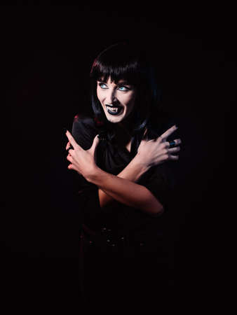 A woman on a black, gloomy background, in black clothes. She looks at the light with a wicked smile, showing her fangs like a vampire and wrapping her arms around herself. Archivio Fotografico