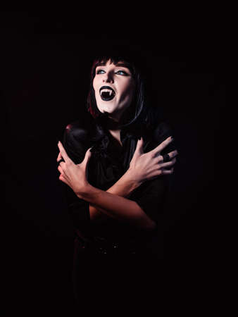 A woman on a black, gloomy background, in black clothes and black makeup. She stares into the light, showing her fangs like a vampire and wrapping her arms around herself.