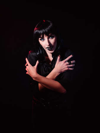 A woman on a black background, in black clothes. She looks at the camera with her mouth open and showing her fangs like a vampire. Her arms are crossed over her chest.