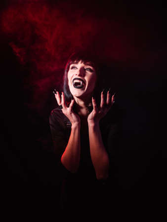 Girl on a black background with red light and artificial smoke in the image of a vampire. She laughs with her mouth open, showing her fangs.