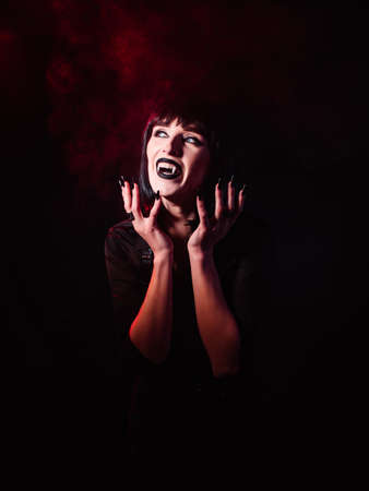A girl in the image of a vampire on a black background with red light and smoke. She looks to the side and laughs with her mouth open, showing her fangs, her hands open to her face.
