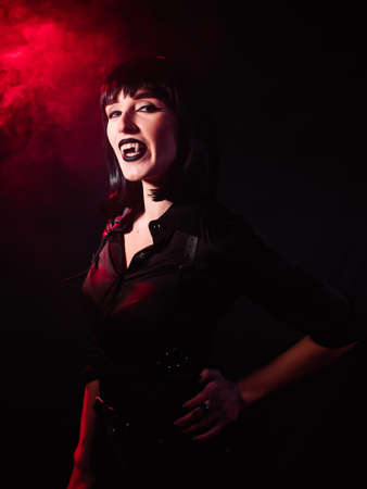 Girl on a black background with red light and artificial smoke in the image of a vampire. She looks haughtily and laughs with her mouth open, showing her fangs.