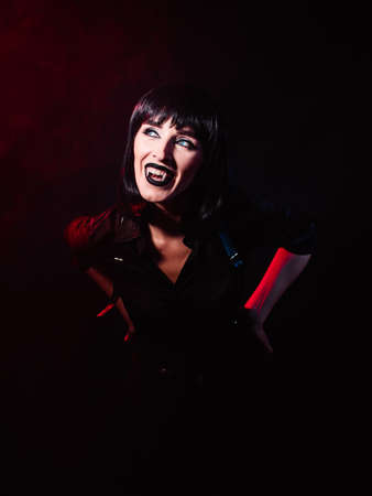 A woman on a black background with red light in the image of a vampire. She looks at the light showing her wings and smiling ominously to the side.