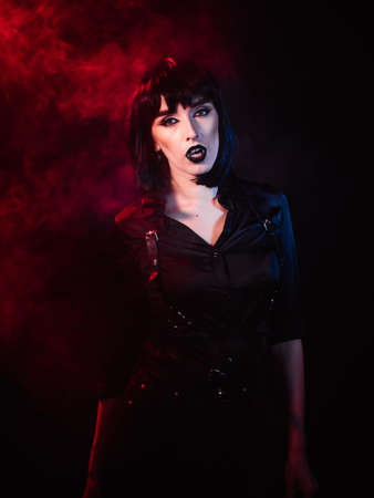 A girl on a black background with colored light and smoke. She wears black clothes, makeup and a harness. She carefully looks at the camera and demonstrates her wings.