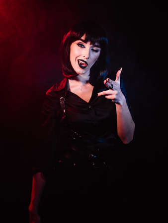 Girl on a black background with red-blue light in the form of a vampire. She winks and gestures with her hands to the camera while showing her fangs.
