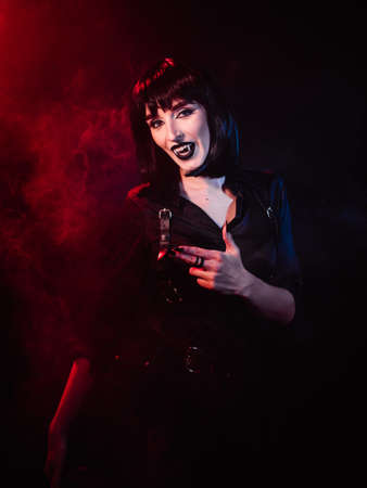 A girl on a black background with red light in the image of a vampire. She shows different hand gestures, laughs and looks at the camera
