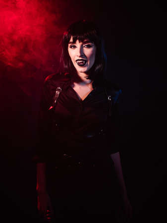 An image of a vampire woman in a black shirt, harness, black wig, her gaze directed towards the camera with a smile from her fangs.