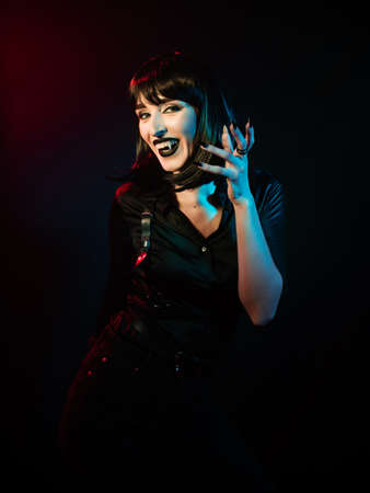 a girl with vampire fangs with black hair in a black shirt and harness raised her hand with long nails in a different-colored light