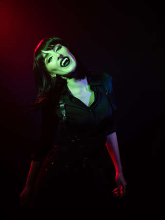 girl in green-red with vampire fangs on a dark background