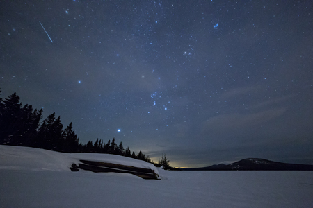 Inverted boat in winter against a starry sky