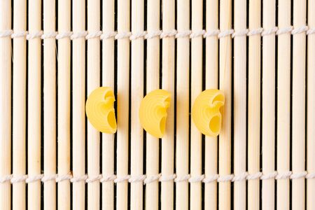 Three macaroni pieces lie against a bamboo Mat Stock fotó