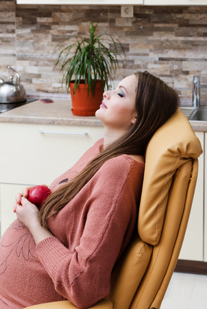 summer fruit: Beautiful pregnant woman eat apple. Indoor photo.