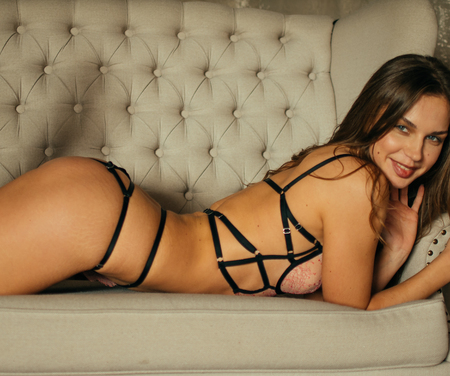 A young mistress in luxurious underwear and high heels is lying on the couch.