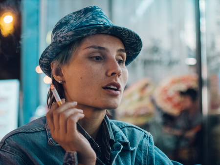 Street portrait of a smoking woman, feeling lonely,sad woman concept.