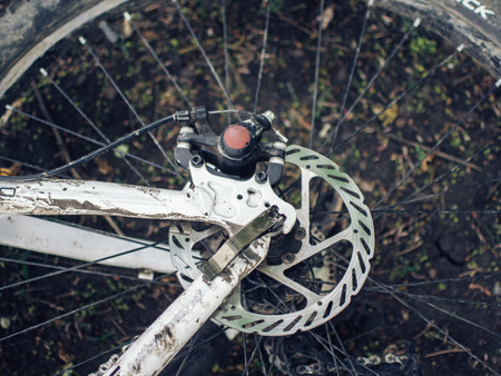 A dirty bike lies on the ground. The details are close-up, the wheels are dirty from a trip in bad weather