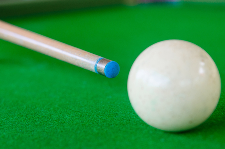 Cue hits the white ball. On the green table.