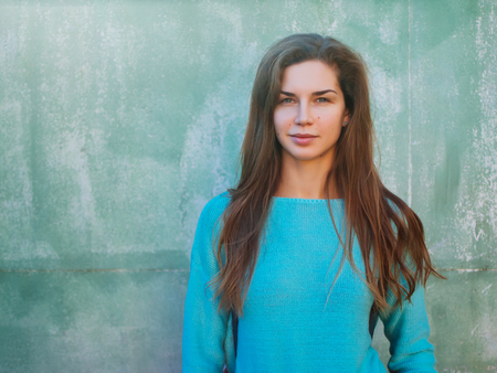 Portrait of a beautiful young caucasian girl. A woman in a blue sweater against the backdrop of a blue wall, a place for text. Standard-Bild - 113380213