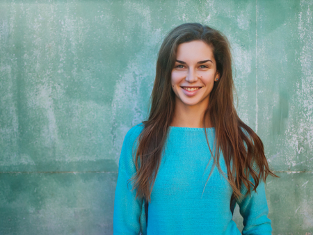Portrait of a beautiful young caucasian girl. A woman in a blue sweater against the backdrop of a blue wall, a place for text. Standard-Bild - 113380214
