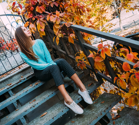 Beautiful young girl in a blue sweater, sitting on the steps of the veranda, enjoying the autumn landscape.