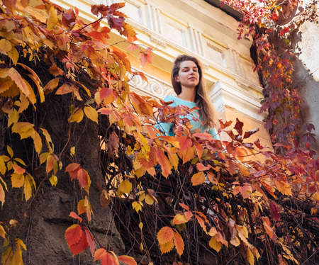 A friendly girl is standing on the balcony of her apartment. Woman enjoying autumn morning.