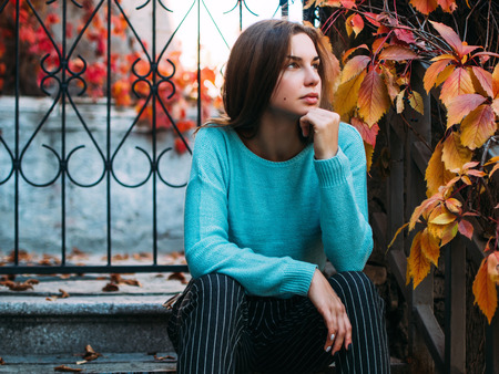 Portrait of a young beautiful woman. The girl on the background of golden autumn, calm and beautiful.