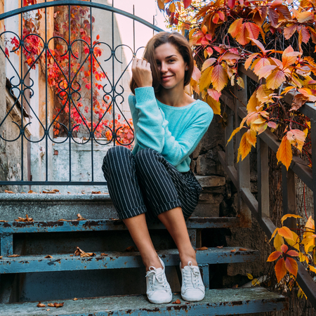 Beautiful young girl in a blue sweater, sitting on the steps of the veranda, enjoying the autumn landscape. Standard-Bild - 113384236