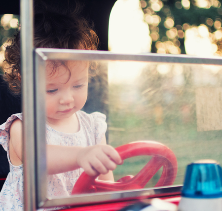 A child behind the wheel of a toy car. Toddler girl in the carousel amusement park.