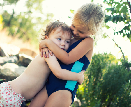 Two sisters hug. Family values, care for younger children. Archivio Fotografico