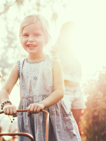 Four-year girl rolls the stroller in the setting sun. Close-up with a glare of the sun in the background. Archivio Fotografico
