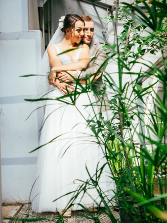 Wedding couple indoors is hugging each other. Beautiful model girl in white dress. Man in suit. Beauty bride with groom. Cute lady and handsome guy Standard-Bild - 117770233